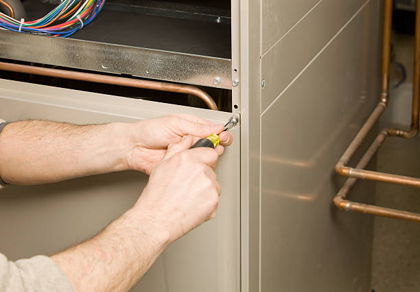 repair technician removing furnace service panel - furnace stock photos and pictures