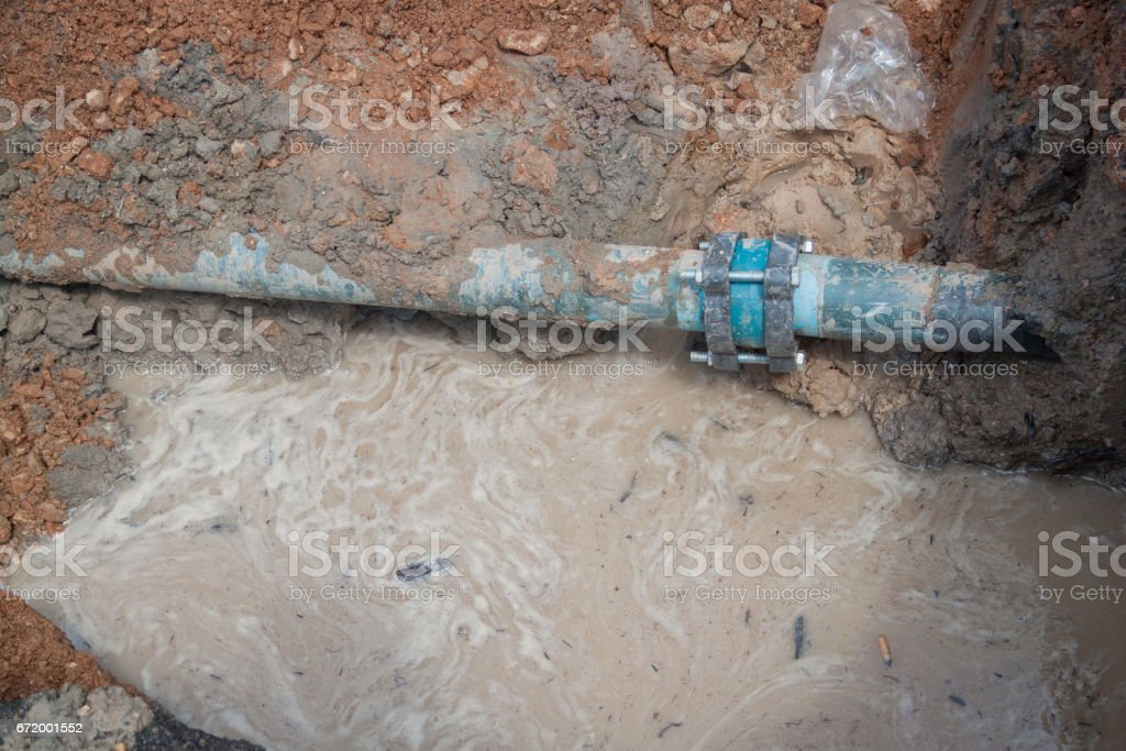 repair the plumbing broken pipe and water flow in hole. stock photo