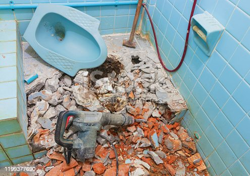 repair toilet old bathroom interior house and pneumatic hammer with Large steel hammer