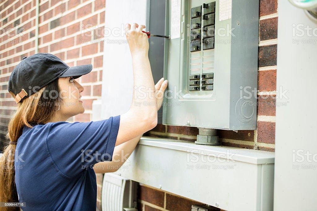 Repair woman, electrician repairing home breaker box. stock photo