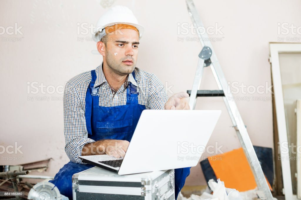 Repairer man looking at the laptop informatoin royalty-free stock photo