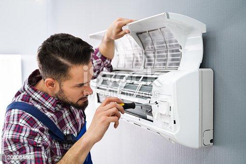 istock Repairer Repairing Air Conditioner 1208084866