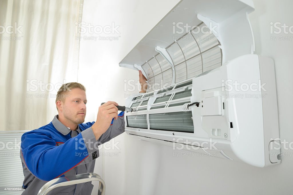 Repairer Repairing Air Conditioner stock photo