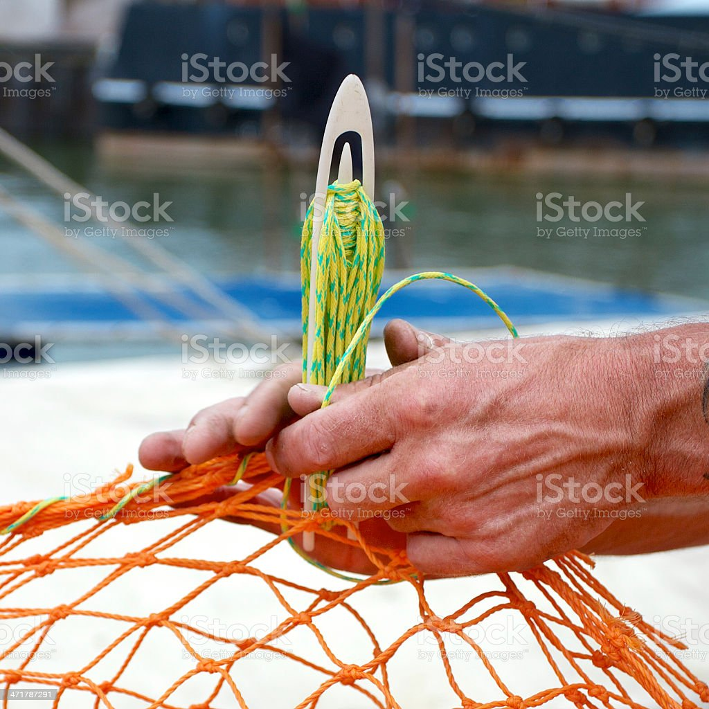 Repairing a fishnet royalty-free stock photo