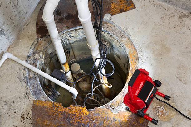 Repairing a sump pump in a basement stock photo