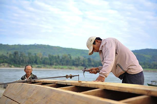 repairing boat Kachin state, Myanmar - December 20, 2008: Burmese man repairs a boat near Ayeyawaddy river at Sinbo township myitkyina photos stock pictures, royalty-free photos & images