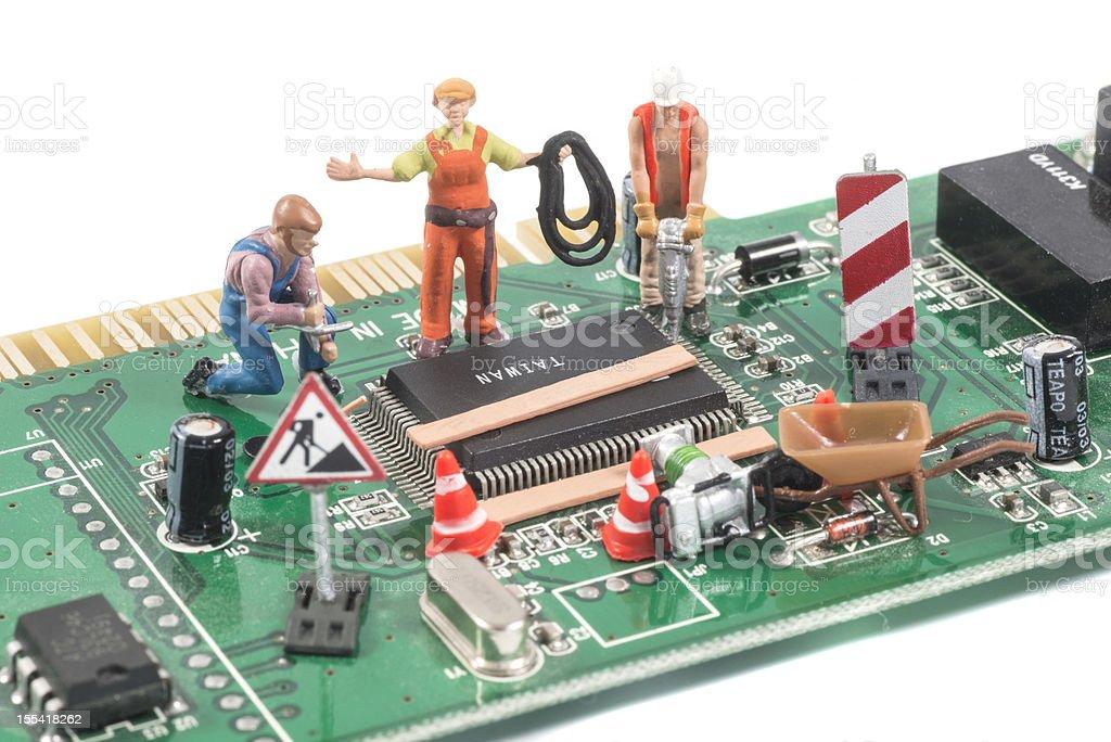 repairing computer equipment with figurines stock photo