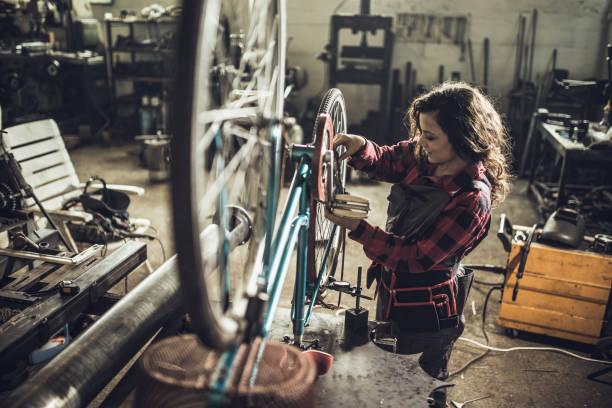 Consertando a bicicleta dela - foto de acervo
