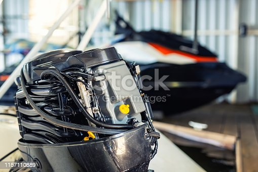 Repairing inflatable motorboat engine at boat garage. Ship engine seasonal service and maintenance. Vessel motor with open cover.