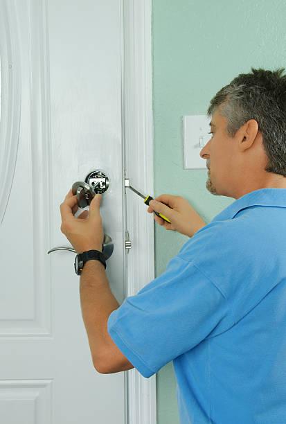 Repairing installing door deadbolt lock on house stock photo