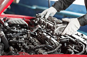 istock Repairing of modern diesel engine, workers hands and tool. Car mechanic looking at engine for analysis symptoms of car at maintenance repair service station 901785402