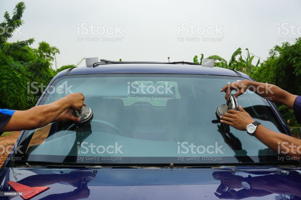 repairing windshield replace windscreen wiper tools fix crack broken front window glass car vehicle services by Glazier. Maintenance repair, replace windshield, windscreen car wiper concept. stock photo