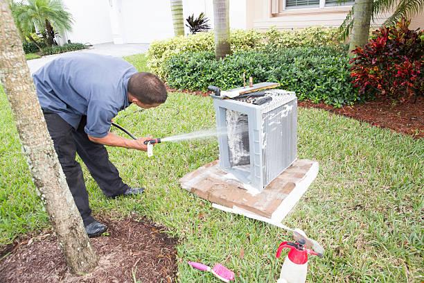 AC repairman acid washing air conditioner coils stock photo