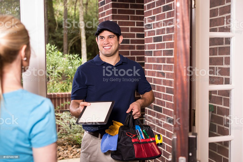 Repairman at customer's front door. stock photo