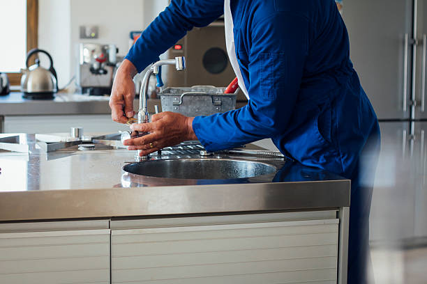 Repairman at Work A shot of a man's hands working on a kitchen sink. He is wearing blue overalls with his tool kit in the background. household fixture stock pictures, royalty-free photos & images