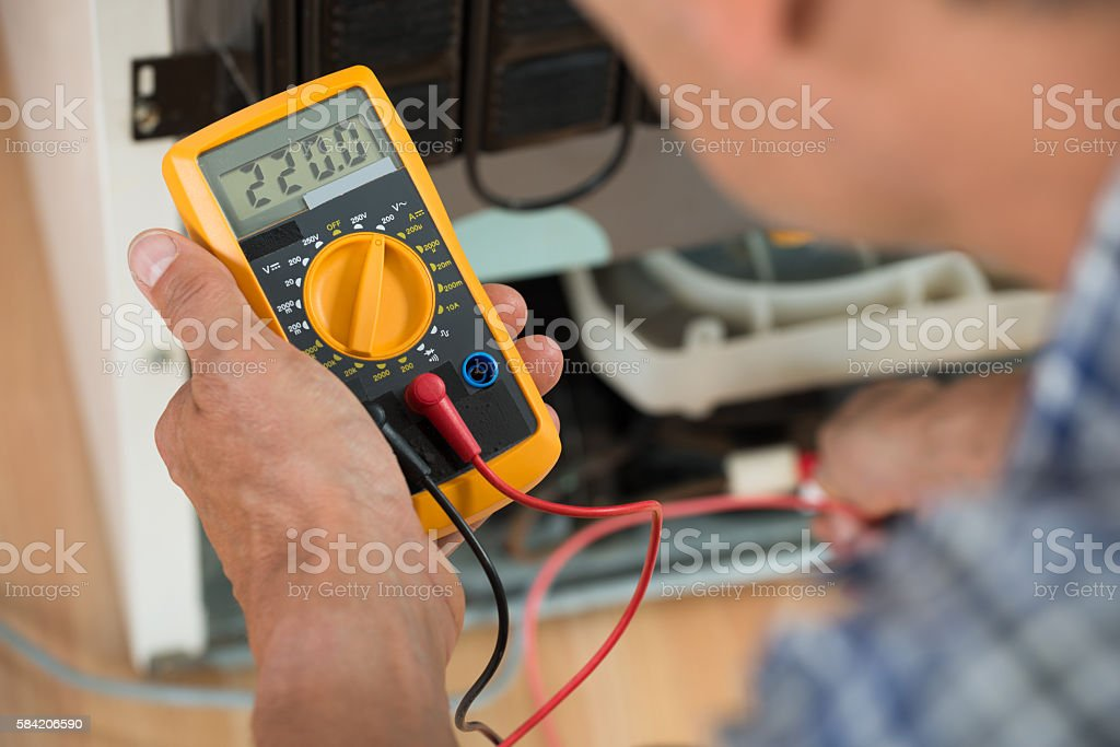 Repairman Checking Fridge With Digital Multimeter stock photo