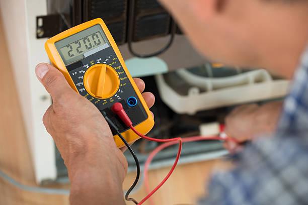 Repairman Checking Fridge With Digital Multimeter stock photo