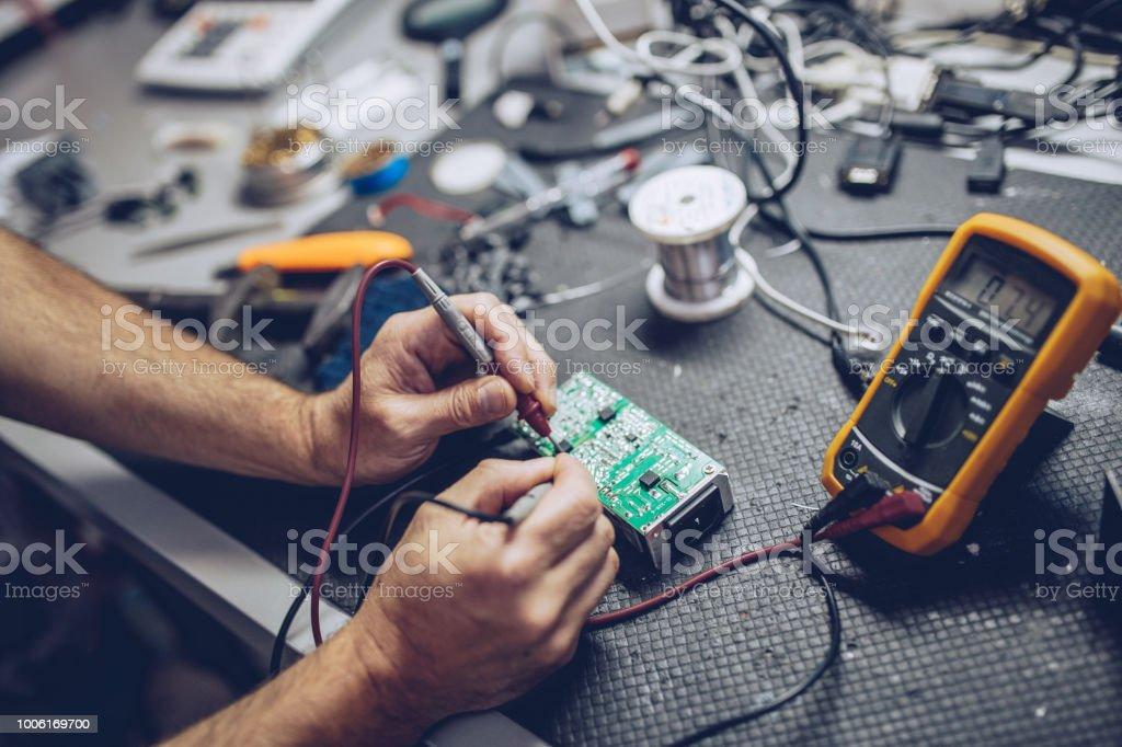 Reparateur verifiëren van spanning met Digitale Multimeter - Royalty-free Alleen mannen Stockfoto