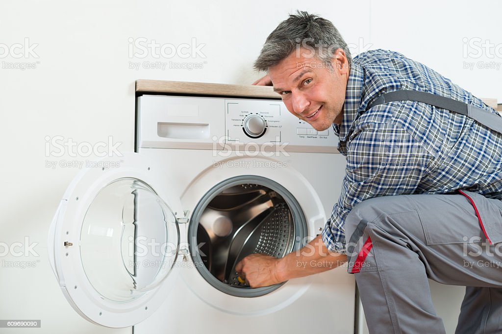Repairman Checking Washing Machine At Home stock photo