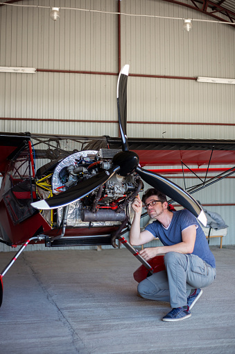 Repairman looking over engine in small aircraft from below. Small red airplane in hangar. Repaiper holding instruments in the hand near the plane engine. Small aviation.