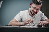 Repairman disassemble motherboard with screwdriver