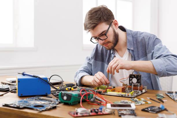 repairman zdemontować płytę główną za pomocą śrubokręta - przemysł elektroniczny zdjęcia i obrazy z banku zdjęć