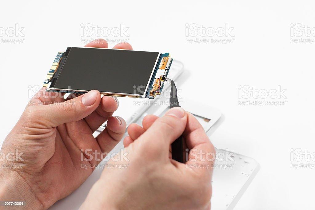 Repairman disassembling smartphone with tweezers stock photo