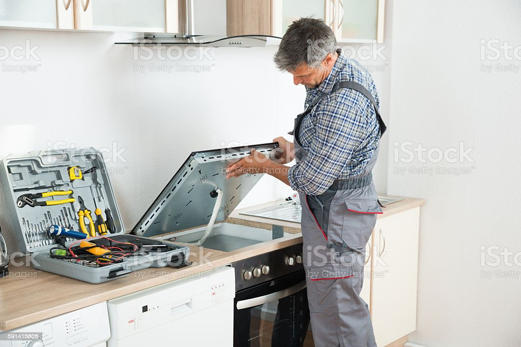 Repairman Examining Stove In Kitchen stock photo