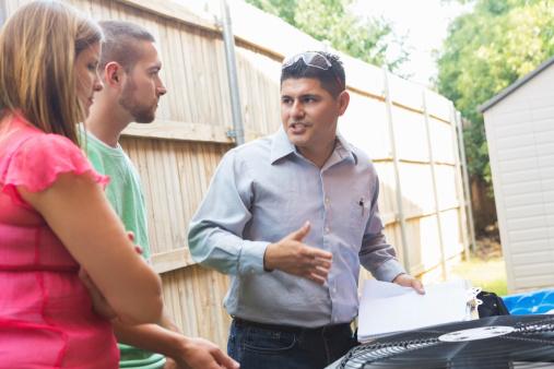 istock Repairman explaining damaged A/C unit to homeowners 509417563