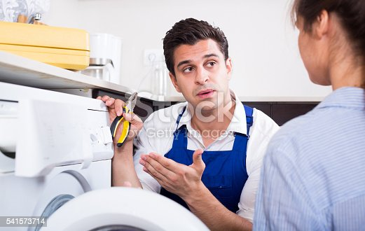 istock Repairman explaining woman how to use washer 541573714