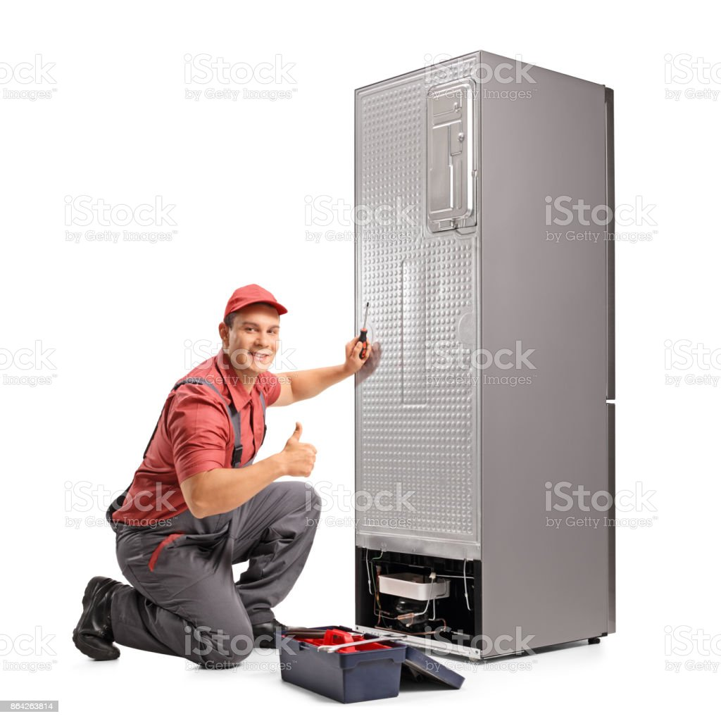 Repairman fixing a refrigerator and making a thumb up sign royalty-free stock photo