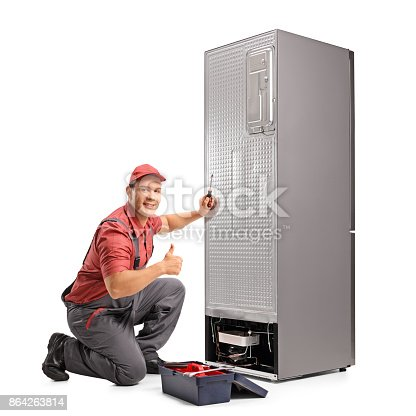 istock Repairman fixing a refrigerator and making a thumb up sign 864263814