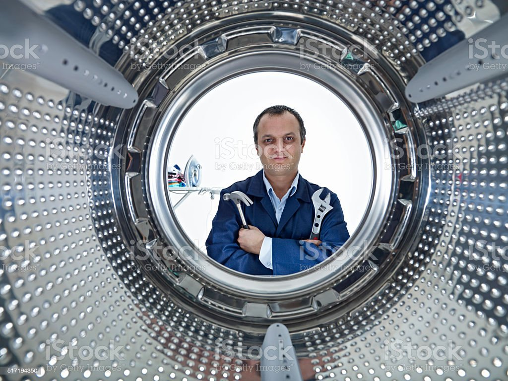 Repairman fixing a washing machine stock photo