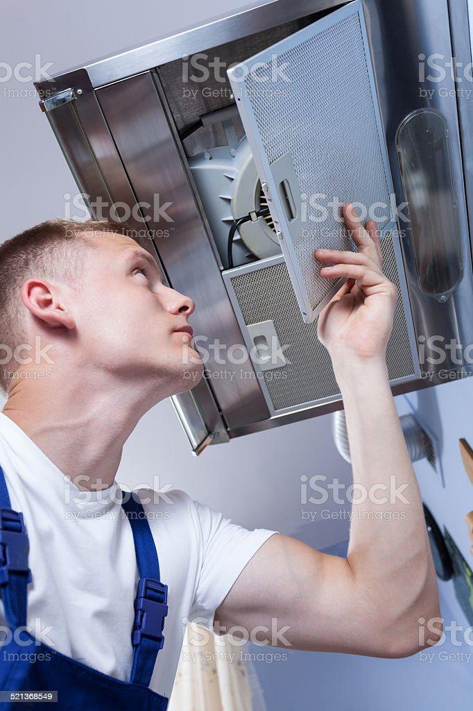 Repairman fixing kitchen extractor fan stock photo