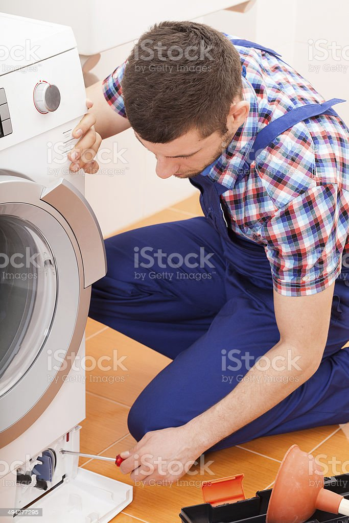 Repairman fixing washing machine stock photo