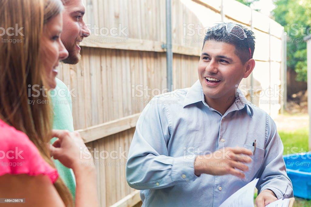 Repairman giving homeowners estimate for costs of home repairs stock photo