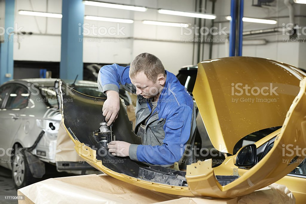 repairman grinding metal body car stock photo