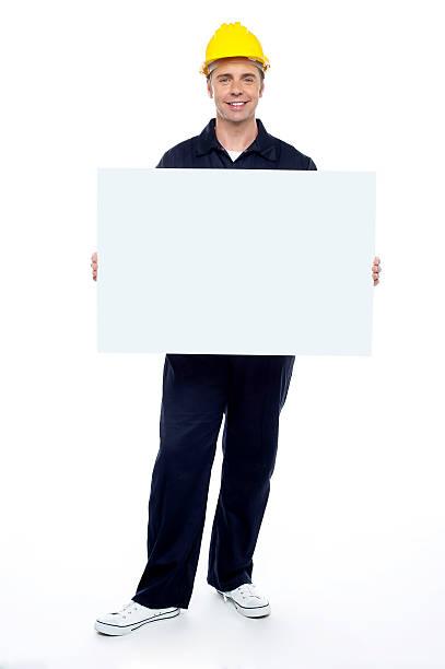 Repairman holding blank billboard, full length portrait stock photo