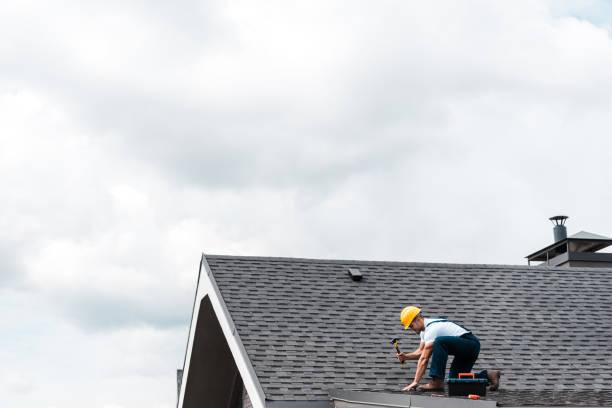 reparman in helm holding hamer tijdens het repareren van het dak - dak stockfoto's en -beelden