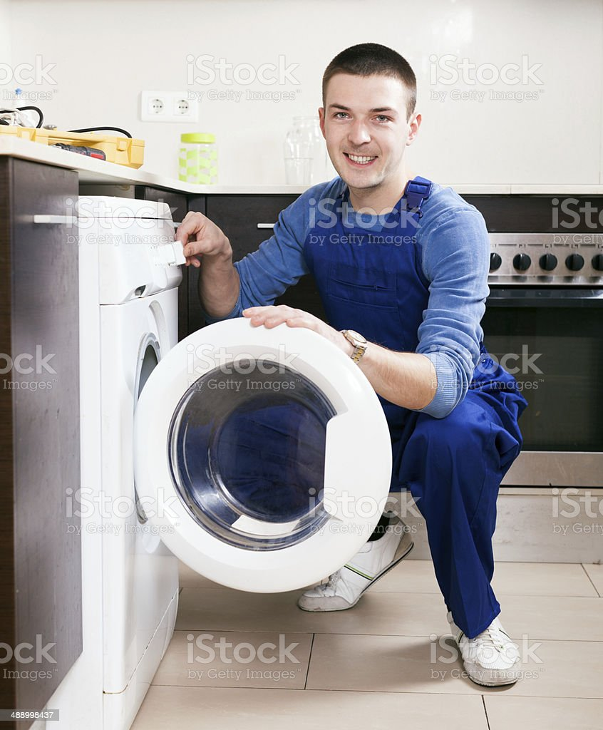 Repairman in uniform at kitchen royalty-free stock photo