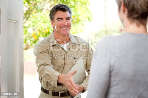 istock Repairman In Uniform Greeting Housewife 155389151
