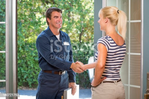 istock Repairman In Uniform Greeting Housewife 180721752