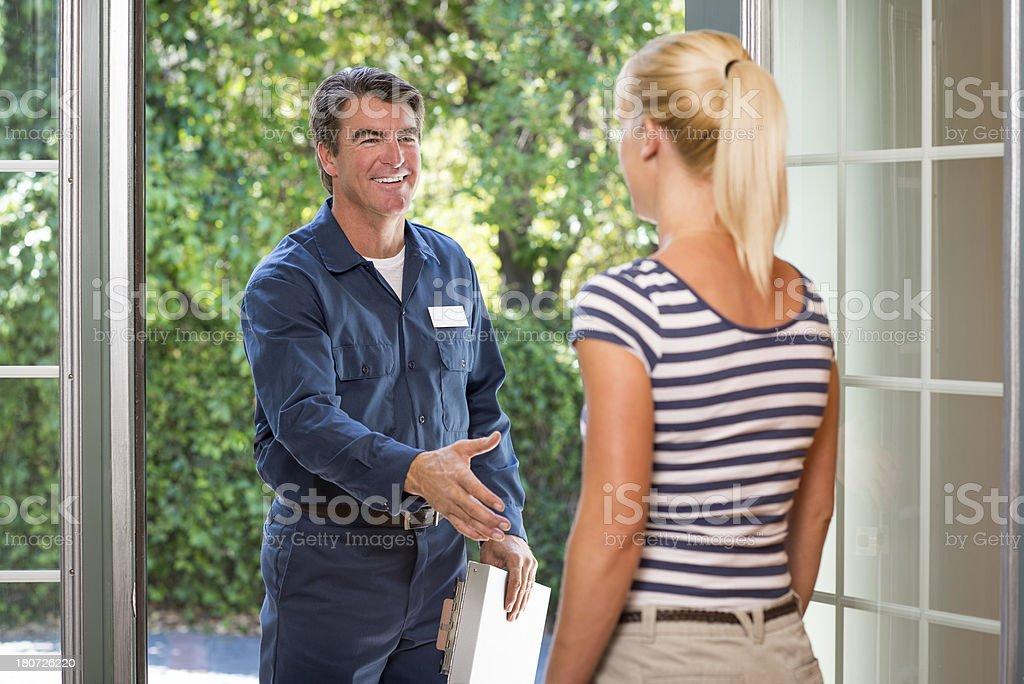Repairman In Uniform Greeting Housewife stock photo