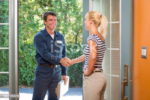 istock Repairman In Uniform Greeting Housewife 180726325