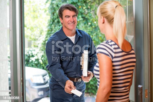 istock Repairman In Uniform Greeting Housewife 181869088