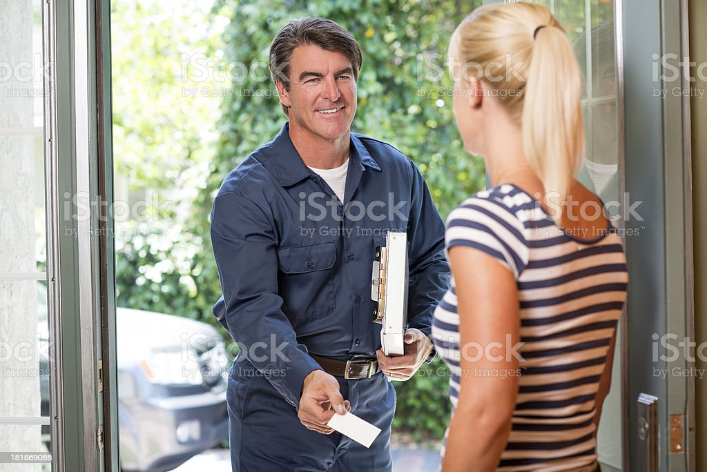 Repairman In Uniform Greeting Housewife stock photo