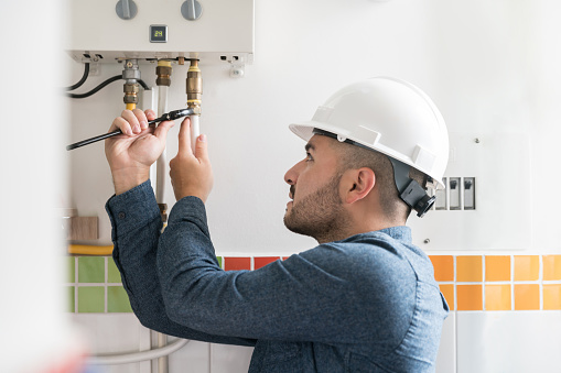 Portrait of a Latin American Repairman installing a natural gas boiler at a house using a wrench - home improvement concepts