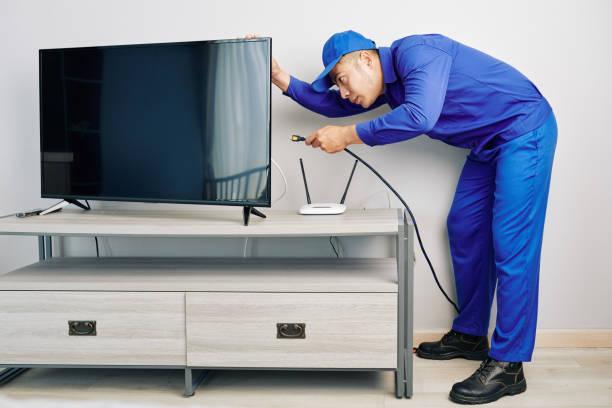 Repairman installing tv set stock photo