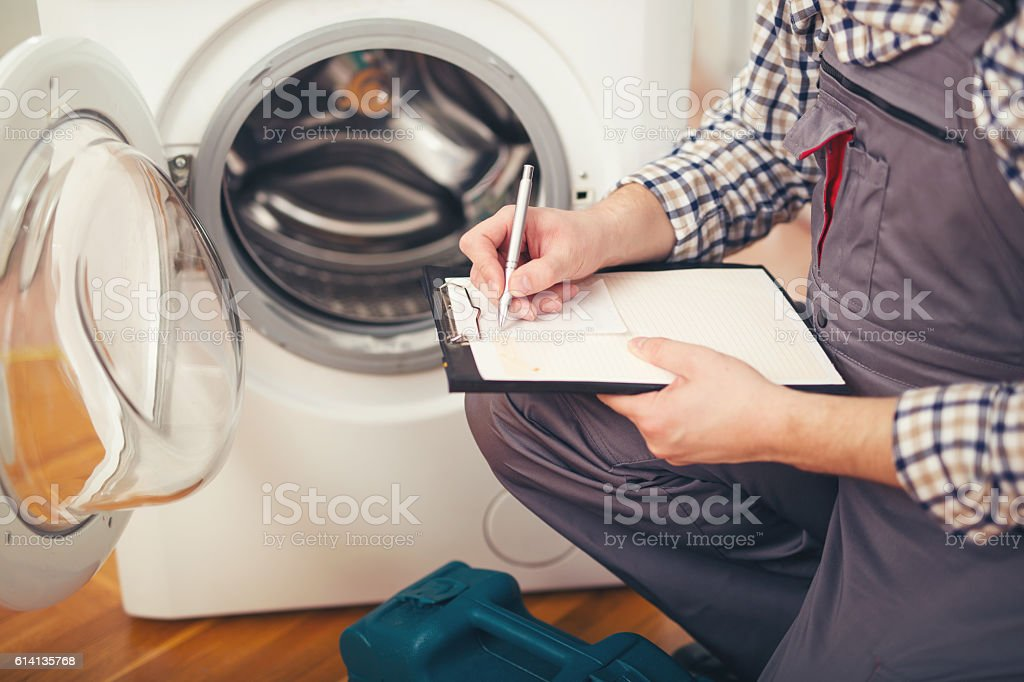 Repairman is repairing a washing machine on the white background stock photo