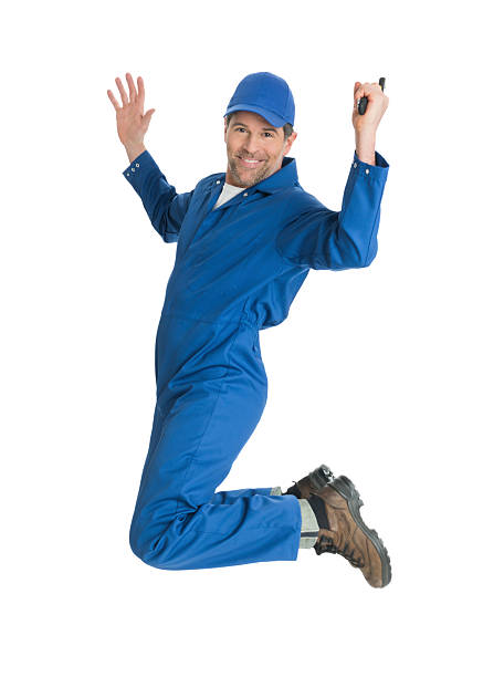 Repairman Jumping Full length portrait of mature repairman holding wrench jumping against white background bib overalls stock pictures, royalty-free photos & images